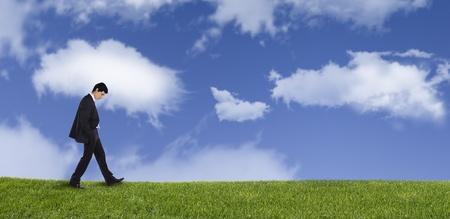 walking alone: Panor�mica de un hombre de negocios caminando sobre el pensamiento de hierba sobre su vida   Foto de archivo