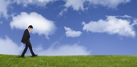 walking down: Panoramic of a businessman walking on the grass thinking about his life