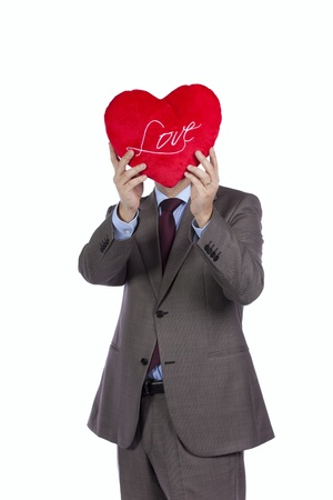 Businessman holding a red pillow with a heart shape in front of his head (isolated on white) photo