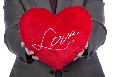 Businessman holding a red pillow with a heart shape photo