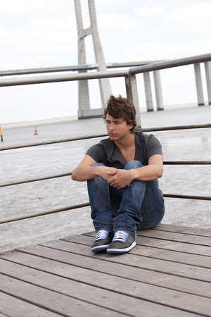 handsome teenager with a sad face sited next to the river photo