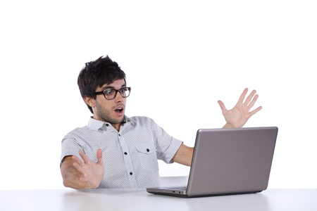 freak out: young man scared with something he see on his laptop computer