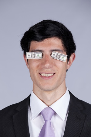 Young businessman with little dollar bills covering his eyes photo