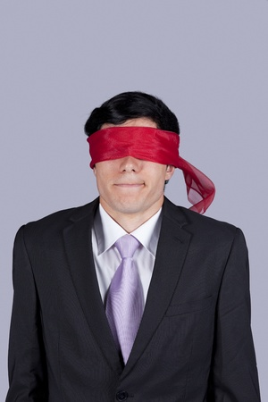 freak out: Hostage businessman with a red blindfold covering his eyes (isolated on gray) Stock Photo