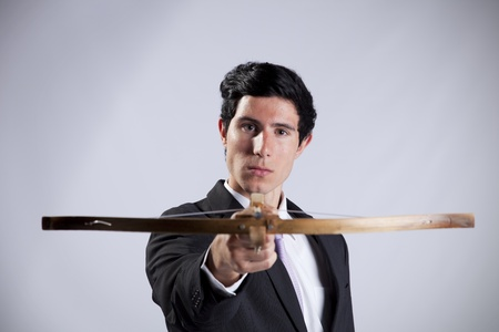 Modern businessman aiming with a crossbow  photo