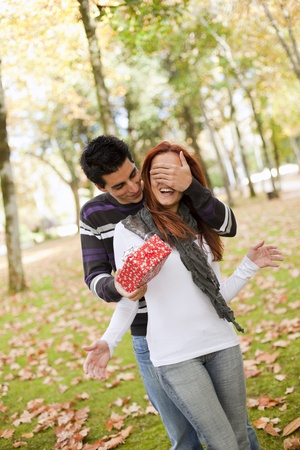covering: man covering the eyes to her girlfriend giving her a present (selective focus with shallow DOF) Stock Photo