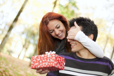 woman covering the eyes to his boyfriend with giving him a present (selective focus with shallow DOF) Stock Photo