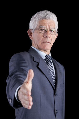 senior businessman making a deal with you (isolated on black) photo
