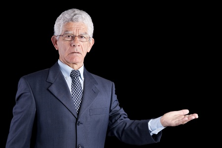 senior businessman showing something with his hands (isolated on black