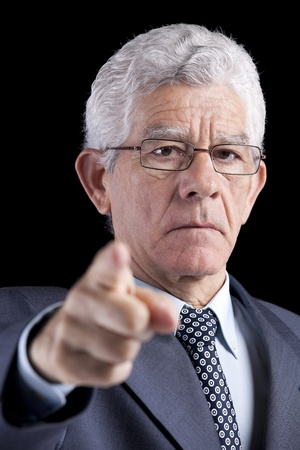 Powerful businessman pointing to you (isolated on black) photo