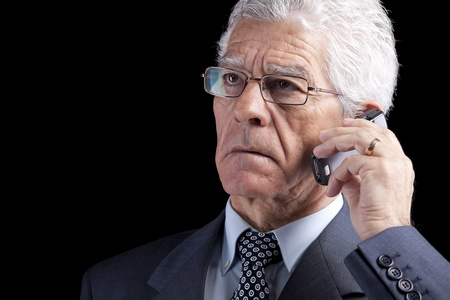 Portrait of a businessman talking at the mobile telephone (isolated on black) photo