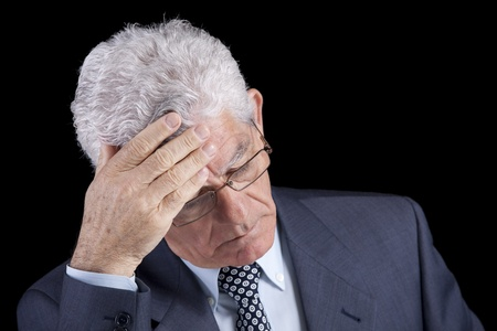 distraught: Senior businessman with an headache (isolated on black) Stock Photo