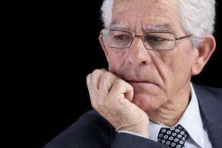 hombre preocupado: Senior empresario pensando con la mano en la barbilla (aislada en negro)