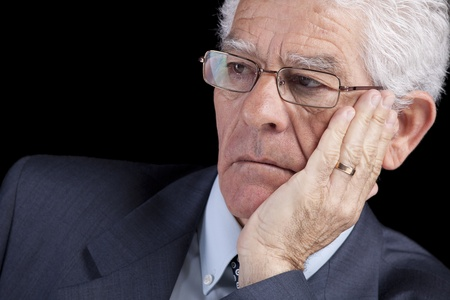 Senior businessman thinking with his hand at the chin (isolated on black) photo