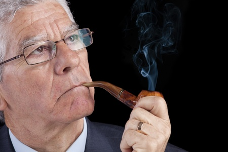 handsome old man: Senior businessman thinking while smoking his pipe (isolated on black)