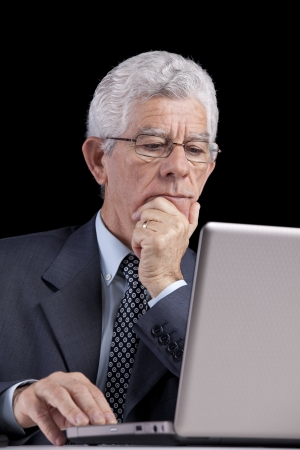 Senior businessman working with his laptop at his office photo