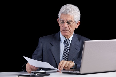 Senior businessman working on some documents at his office photo