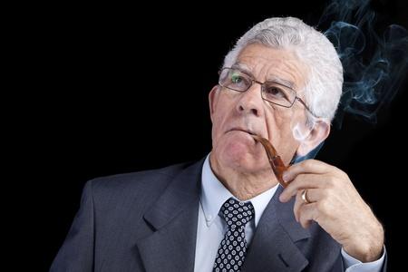 persona fumando: Senior empresario pensando mientras fumando su pipa (aislado en negro)