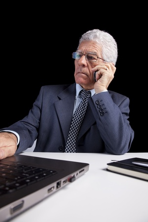 Portrait of a businessman talking at the mobile phone and looking to his laptop (isolated on black) photo