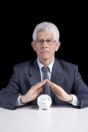 Senior businessman saving some money for his retirement (isolated on black) photo