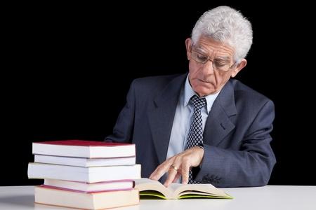 Senior teacher reading some books (isolated on black) photo
