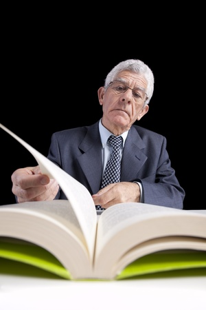 Senior businessman holding a page from an open book (isolated on black) photo