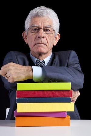 Senior teacher portrait behind some books (isolated on black) photo