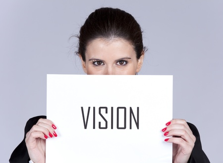 hiding face: Businesswoman peeking behind a paper with the word Vision Stock Photo