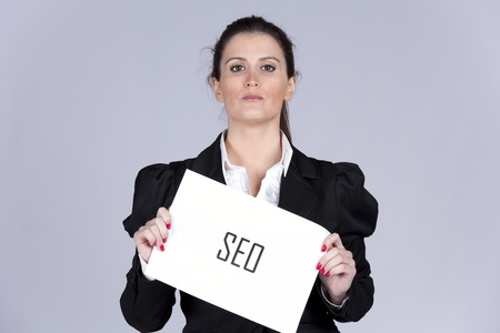 Businesswoman holding a paper with the word SEO Stock Photo - 10030077