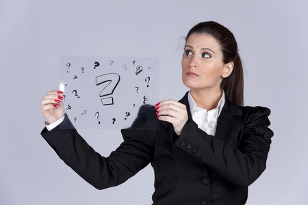Businesswoman holding a acetate with lots of question marks photo