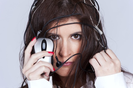 cybernetic: Beautiful young woman with lots of computer cables over her head, peeking behind a computer mouse Stock Photo