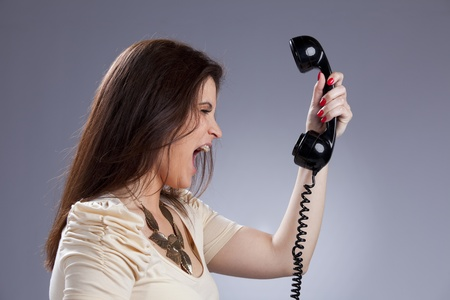 Furious young woman shouting to the telephone handset photo