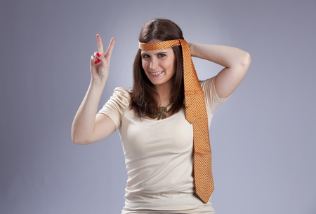 60s hippie: Young woman with a necktie on her head, gesturing the peace and love sign with her fingers Stock Photo