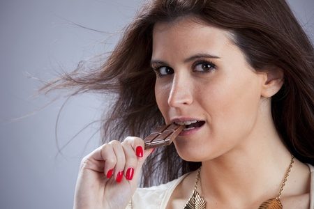 Young beautiful woman eating some chocolate photo