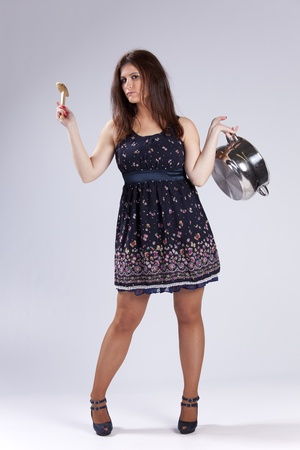 Fashion beautiful woman holding a kitchen pan and a wood spoon photo