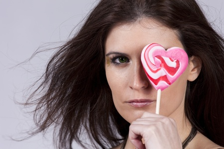 Beautiful woman holding a heart shape candy hiding her left eye photo