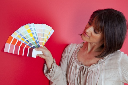woman next to a red wall looking to a color paint palette (selective focus) Stock Photo - 10029871