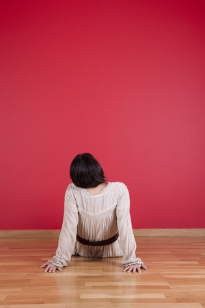 Woman sitted on the floor looking up to a red wall Stock Photo - 10029942