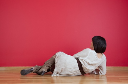 Woman lying on the floor looking to her fresh new red wall Stock Photo - 10029940