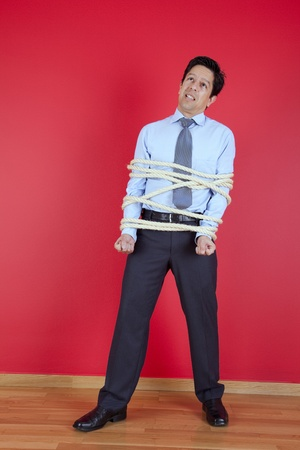 tied up: Businessman tied up with a rope struggle to get free