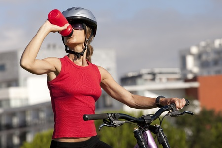 water vehicle: young woman drinking water after doing some bicycle exercise