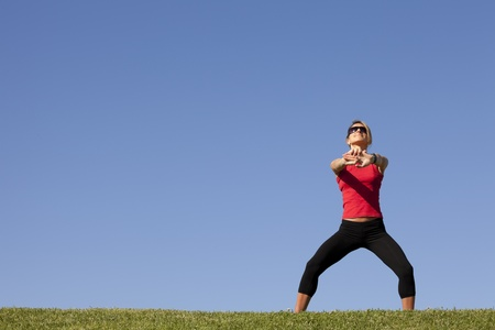 young woman doing some exercise at the park (lots of copyspace) photo