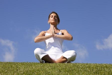 young woman enjoying nature in a yoga lotus pose photo