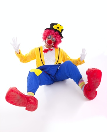 Funny circus clown falling on the floor (isolated on white) photo
