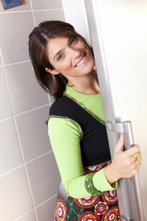 abriendo puerta: Mujer feliz en casa abrir la puerta de la nevera  Foto de archivo