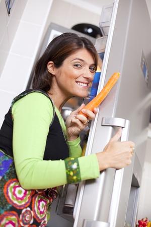 abriendo puerta: Feliz mujer en casa abrir la puerta de la nevera a comer una zanahoria (enfoque selectivo con DOF superficial) Foto de archivo
