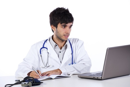 young male doctor: happy young doctor working at his desk (isolated on white) Stock Photo