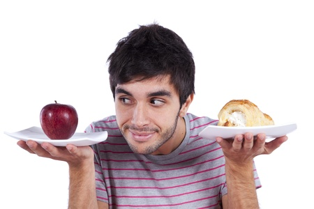 man thinking what to eat between an apple and a cake (isolated on white)
