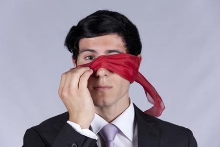 blindfold: Lost businessman peeking behind a blindfold