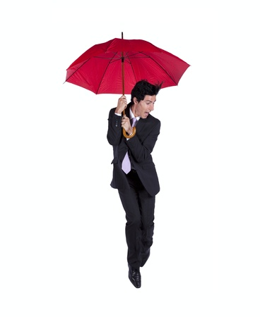 man holding himself to a red umbrella with fear (some motion blur) photo